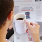 Adult Male Drinking Coffee Reading A Newspaper Royalty Free Stock Image