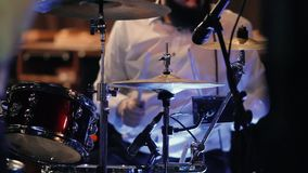 An adult male drummer plays on a drum kit at a rock concert. stock video footage