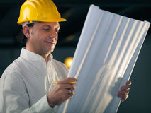 Adult male engineer holding building blueprints Stock Photos