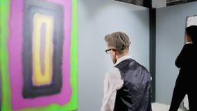Man is enjoying contemporary abstract picture and music in his earpieces. Adult male guest of art gallery is listening to music by headphones, sitting in hall stock video footage