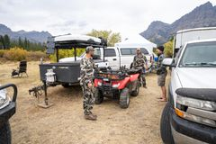 Adult male hunters gather around base camp for deer hunting near Dubois Wyoming. Adult male hunters gather around base camp, discussing plans for the day. Trucks royalty free stock image