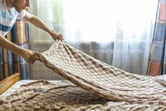 Adult male making a bed, hotel room service concept f royalty free stock photos