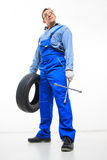 Adult male mechanic with a wrench and tire Royalty Free Stock Image