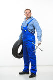 Adult male mechanic with a wrench and tire Royalty Free Stock Images