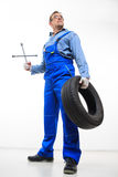 Adult male mechanic with a wrench and tire Royalty Free Stock Photography