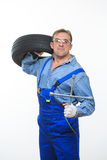Adult male mechanic with a wrench and tire Royalty Free Stock Photos
