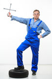 Adult male mechanic with a wrench and tire Stock Images