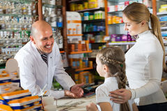 Adult male pharmacist helping customers. Adult male pharmacist wearing white coat standing next to shelves with medicine and helping customers Royalty Free Stock Photo