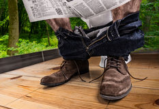 Adult male reading newspaper while sitting on the toilet seat. Adult male wearing jeans and shoes reading newspaper while sitting on the toilet seat Royalty Free Stock Photo