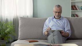 Adult male sitting on couch and booking a hotel room for vacation on tablet. Stock footage stock footage