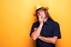 Adult male smoking cigarette and wearing hat. Adult male smoking cigarette and wearing cowboy hat. Bad habbits never die Royalty Free Stock Photography