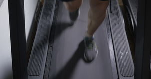 Adult male in sneakers walking on a treadmill. And then begins to run. Feet closeup stock video