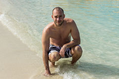 Adult Male Squatting in Ocean With Right Hand in the Water Royalty Free Stock Image