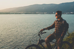 Adult Male Standing With Bike On Coast And Enjoying View of Nature Sunset Vacation Traveling Relaxation Resting Concept Stock Image