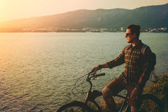 Adult Male Standing With Bike On Coast And Enjoying View of Nature Sunset Vacation Traveling Relaxation Resting Concept. Adult Male cyclist with a backpack in Royalty Free Stock Photography
