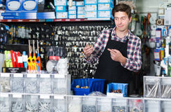 Adult male standing near the counter and selling details. For plumbing in hardware shop Royalty Free Stock Image