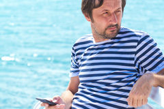 Adult male in striped sailor shirt using mobile at sea. Adult caucasian male in striped sailor shirt using mobile phone at seaside beach to send a SMS message Stock Photos