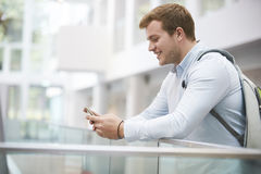 Adult male student using smartphone in university interior Stock Photo