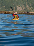 Adult male in sunglasses and baseball cap holding a paddle and rowing sitting in a kayak Royalty Free Stock Photo