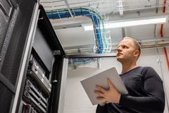 Adult Male Technician Holding Digital Tablet and Analysing Servers in Datacenter. Confident male technician holding digital tablet standing and analysing server royalty free stock photo