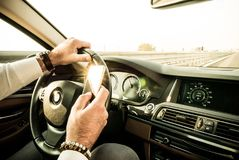 Adult male texting while driving. Dangerous behaviour Royalty Free Stock Photos