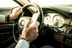 Adult male texting while driving. Dangerous behaviour Royalty Free Stock Photography