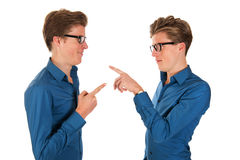 Adult male twins. Identically adult male twins pointing to each other in studio Stock Photos