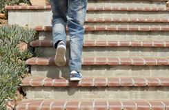 Adult male walking up cement tiled stairs. Young male walking up cement stairs wearing jeans and shoes Stock Photo