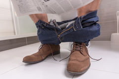 Adult male wearing jeans and shoes reading newspaper while sitti. Ng on the toilet seat in the modern tiled bathroom at home Royalty Free Stock Image