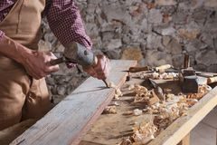 Woodworker using chisel to smooth down wood. Adult male woodworker wearing plaid shirt and overalls using chisel and mallet to smooth down wood beam stock images
