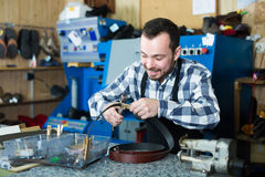 Adult male worker shaping new hole in belt Stock Photo