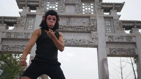 Adult man acting silly funny in monkey mask in front of ancient temple somewhere in asia.  stock footage