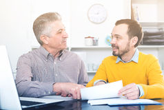 Adult man and agent discuss contract. Adult male and insurance agent to discuss and sign contract in office royalty free stock photography