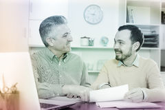 Adult man and agent discuss contract. Mature men and young agent study and sign insurance agreement in office royalty free stock photos