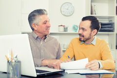 Adult man and agent discuss contract. Mature men and young agent study and sign insurance agreement in office royalty free stock images