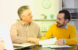 Adult man and agent discuss contract. Adult men and young agent discuss and sign insurance contract in office royalty free stock photos