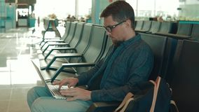 Adult man in airport alone. Portrait of a man in eyeglasses using laptop in airport terminal area alone. Man waiting for flight in a hall, tourist travels by stock video