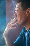 The adult man the Asian  smokes a cigarette Royalty Free Stock Photos