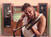 Adult man with beard sings to the vacuum cleaner Royalty Free Stock Photography