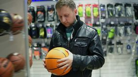 An adult man in black leather jacket choosing a basketball ball in a sports store.  stock footage