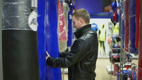 An adult man in black leather jacket choosing a punching bag in a sports store.  stock video