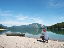 Adult man in blue shirt at old fishing paddle boat at mountains lake stock photography