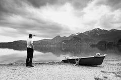 Adult man in blue shirt walk at old fishing paddle boat at mountains lake coast. Stock Photo