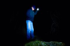 Adult man in blue wearing looking for something in wet grass with light in hand. Scary or fairytale night stock image