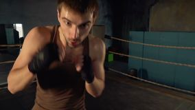 Adult man boxing with shadow on the ring. In industrial gym. Lightweight kickboxer training POV slow motion stock footage