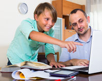 Adult man and boy with laptop indoors Stock Images