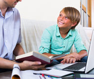 Adult man and boy with laptop indoors Stock Photo