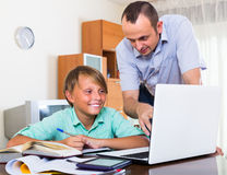 Adult man and boy with laptop indoors Royalty Free Stock Image