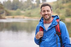 Adult man on a camping holiday standing by a lake smiling to camera, portrait, Lake District, UK stock photos