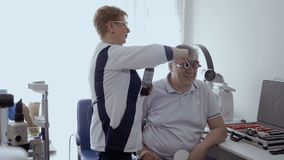 Adult man check his eyesight with optical trial frame in oculist office. Doctor check man`s sight with optical trial frame. Senior man has a bad eyesight and stock footage